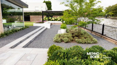 Moderne-tuin-aan-het-water-lounge-pergola-veranda-dakbomen-tuinmuurtje-potten